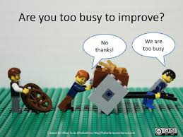 Lego characters carrying heaving load with another character offering to help with wheels; emphasizing too busy to improve