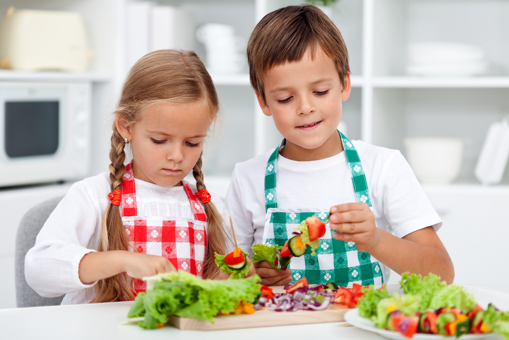 Young boy and girl in child care program learning to make healthy snacks and meals