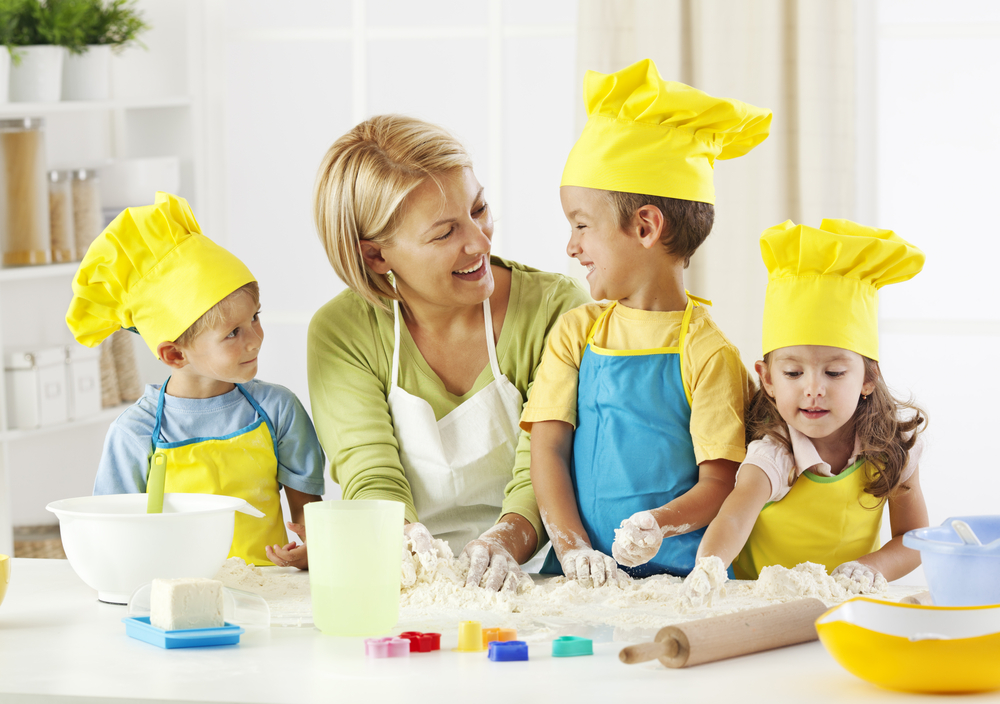 Preschool children in child care program with teacher learning to cook