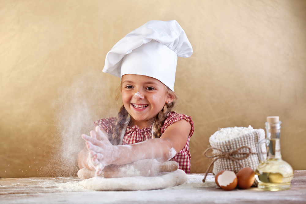 Young child learning to make pizza dough