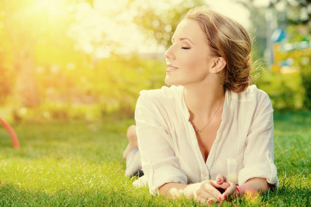 Woman relaxing and meditating on the grass in a beautiful park
