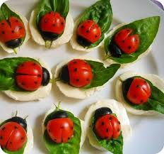 Healthy snack food ladybugs made by young children using cheese and tomatoes