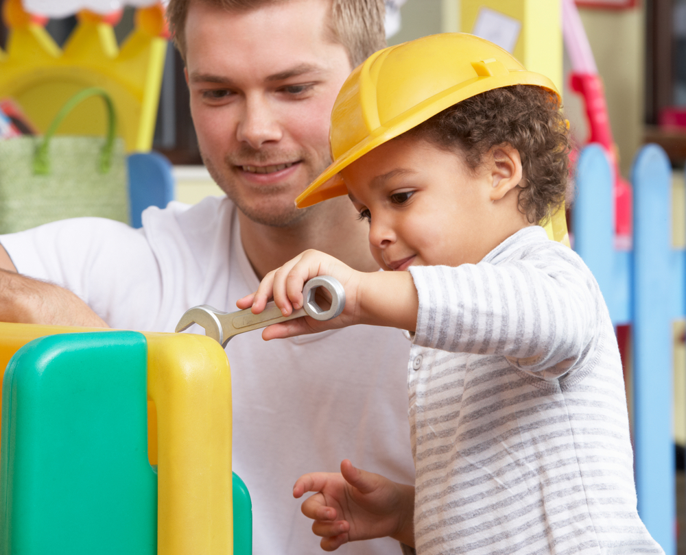 Male teacher showing young child how to use tools in preschool